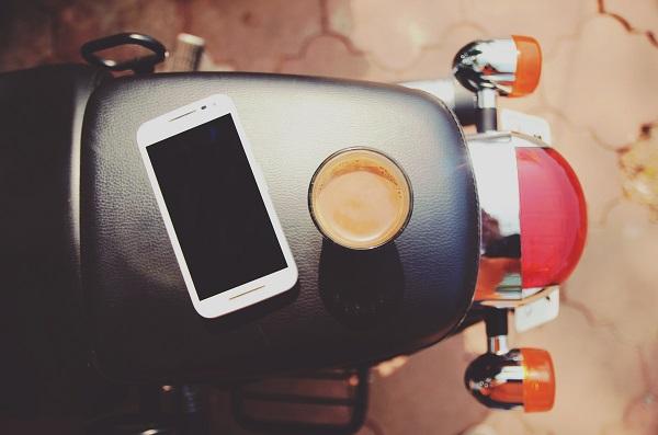 Moto avec un téléphone mobile et le café